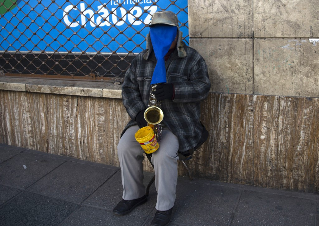 A street musician wears a cloth over his face as protection amid the new coronavirus pandemic as he plays his saxophone for tips in La Paz, Bolivia, W...