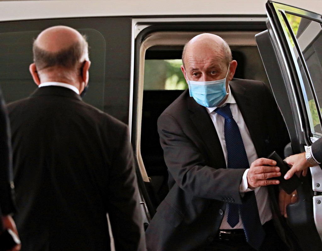 French Foreign Minister Jean-Yves Le Drian, right, wearing a mask to help prevent the spread of the coronavirus, arrives to meet his Iraqi counterpart...