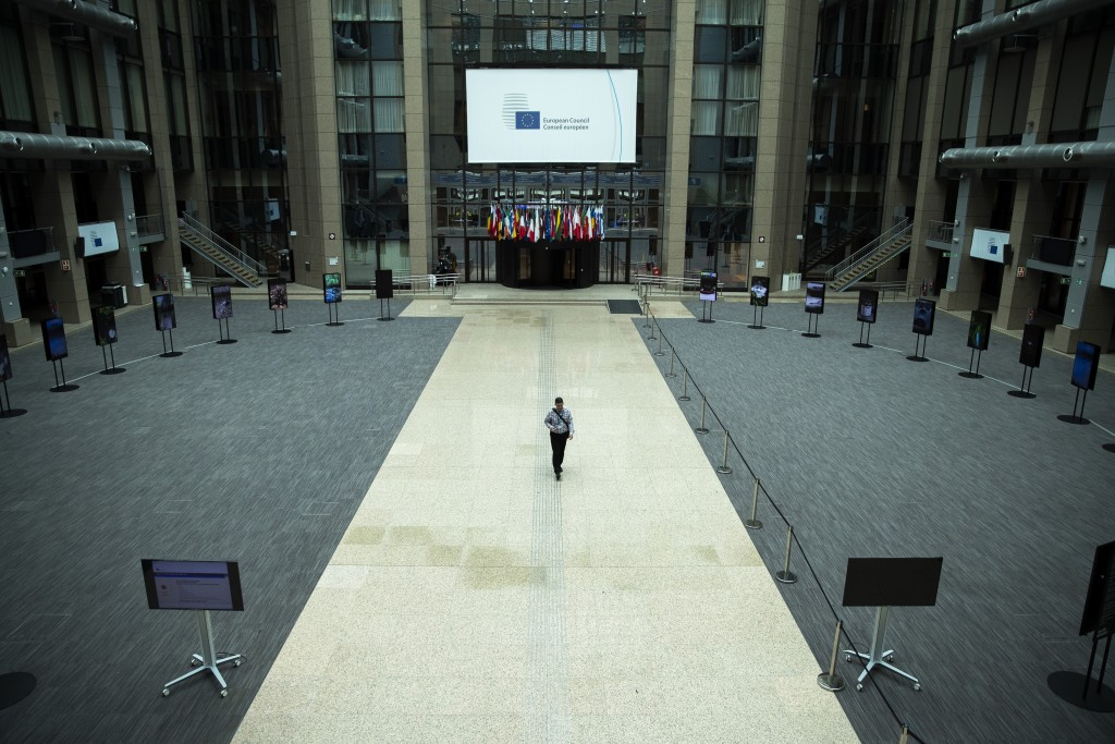 A man walks in the empty atrium, usually full of tables for journalists to work during EU summits, at the European Council building in Brussels, Thurs...