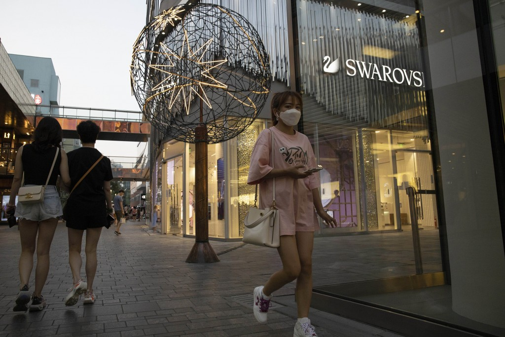 Shoppers pass through an affluent shopping district in Beijing on Tuesday, July 14, 2020. China's economy rebounded from a painful contraction to grow...