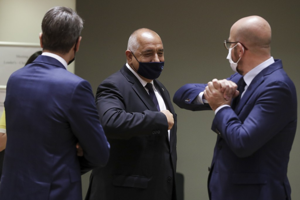 European Council President Charles Michel, right, greets Bulgaria's Prime Minister Boyko Borissov, center, with an elbow bump during a round table mee...
