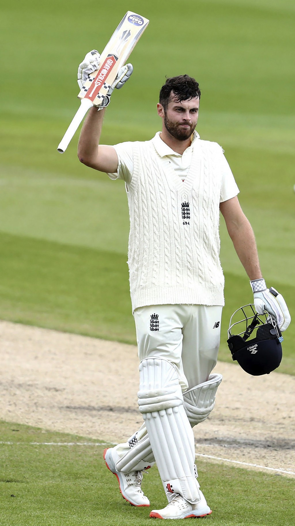 England's Dom Sibley raises his bat to celebrate scoring a century during the second day of the second cricket Test match between England and West Ind...