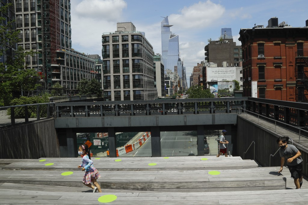 Children wearing protective masks during the coronavirus pandemic play at the High Line Park, Thursday, July 16, 2020, in New York. The High Line open...