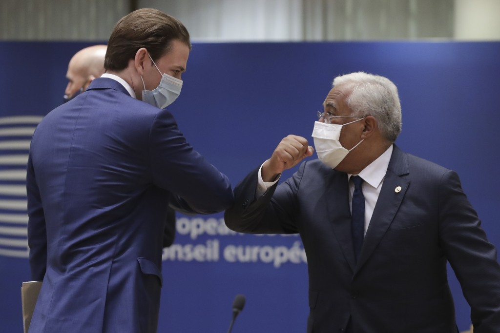 Austria's Chancellor Sebastian Kurz, left, greets Portugal's Prime Minister Antonio Costa, right, with an elbow bump during a round table meeting at a...