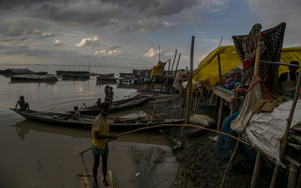 Indian flood affected people take shelter at temporary structures near their submerged house along river Brahmaputra in  Morigaon district, Assam, Ind...