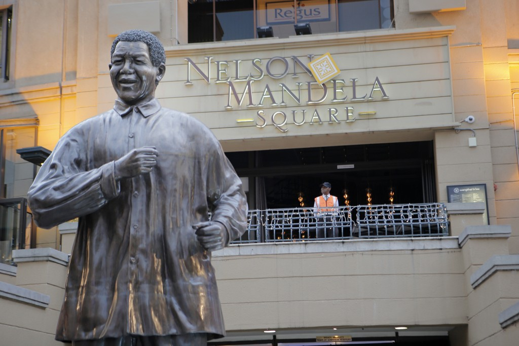 FILE - In this Dec. 12, 2013 file photo, a giant statue of former President Nelson Mandela overlooks Mandela Square in Johannesburg. Mandela's fight f...