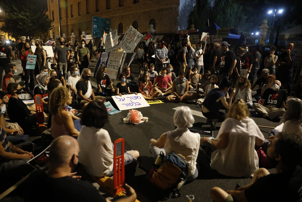 Demonstrators sit during a protest in front of Israel's Prime Minister's residence in Jerusalem, Thursday, July 16, 2020. Hundreds of protesters gathe...