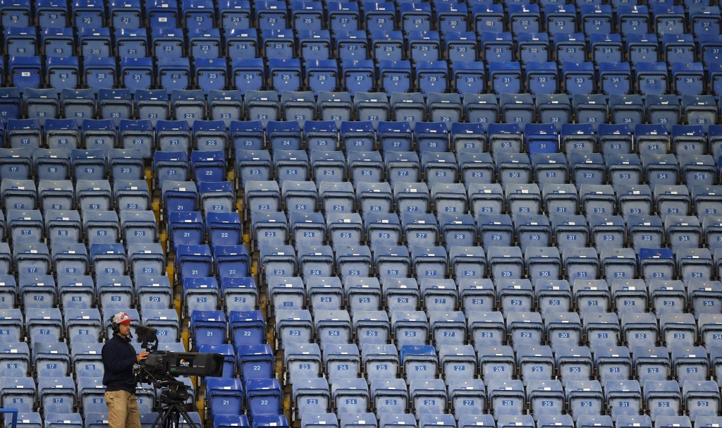 FILE - In this Tuesday, July 14, 2020 file photo, a television cameramen films in front of the empty stands during the English Premier League soccer m...