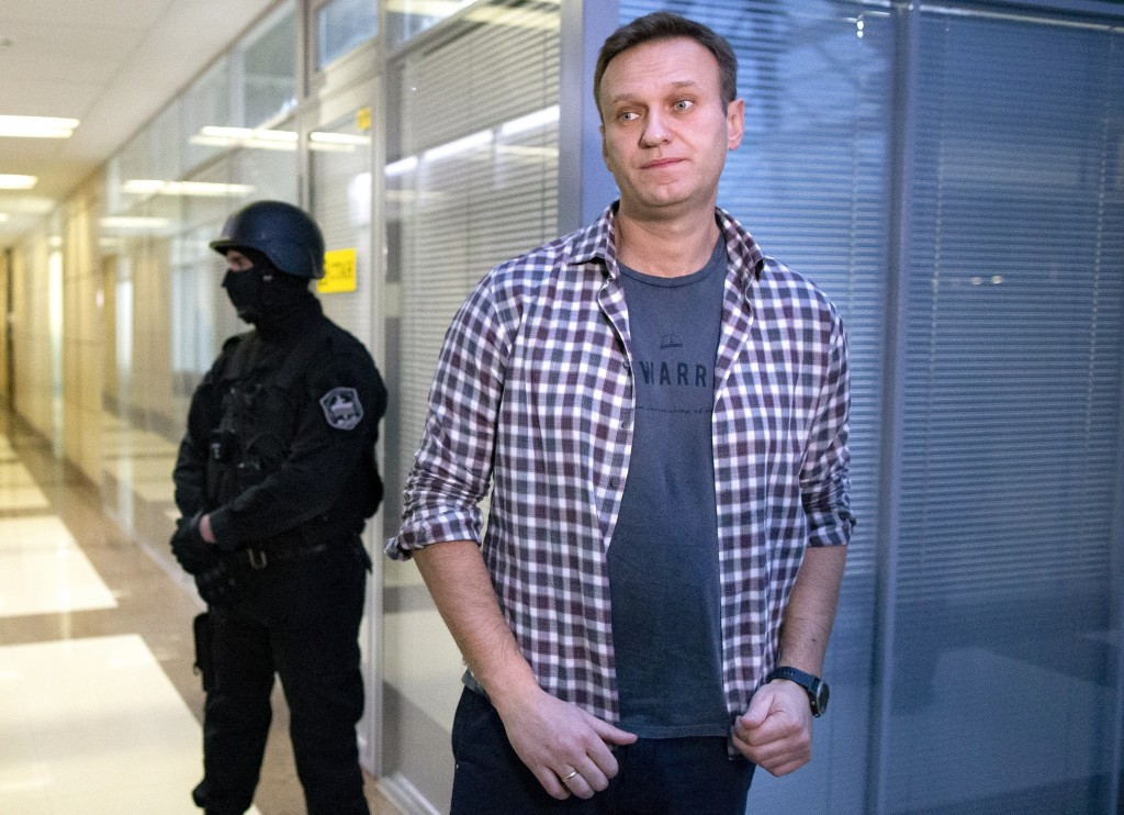FILE- In this file photo taken on Thursday, Dec. 26, 2019, Russian opposition leader Alexei Navalny speaks to the media in front of security officers ...