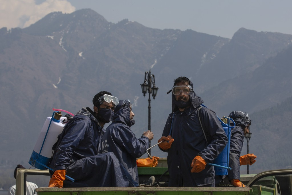 Srinagar Municipal Corporation staff travel in a vehicle after spraying disinfectants in a tourist area as a precautionary measure against COVID-19 in...