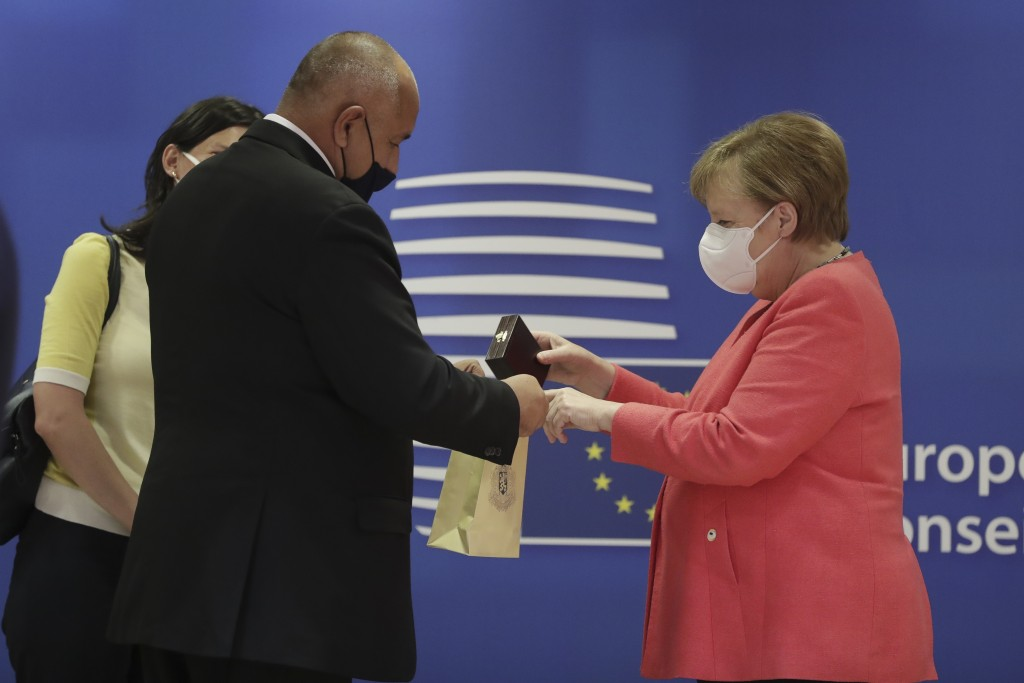 German Chancellor Angela Merkel, right, puts a gift in a bag as she speaks with Bulgaria's Prime Minister Boyko Borissov during a round table meeting ...