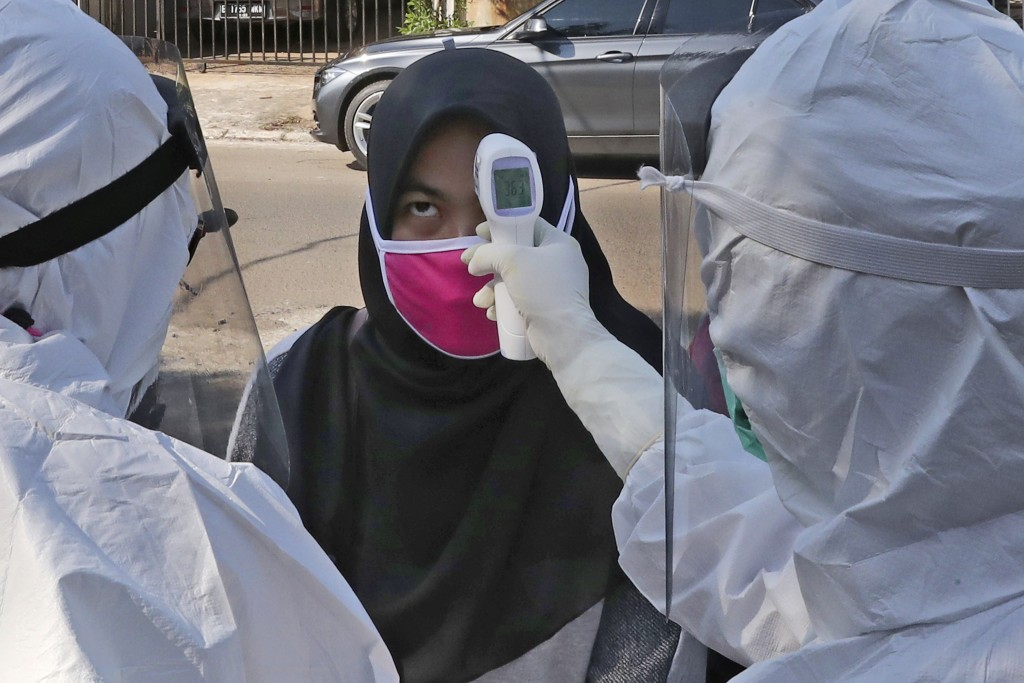 Health workers take the body temperature reading of a woman during a mass test for the new coronavirus in a neighborhood in Tangerang, Indonesia, Frid...