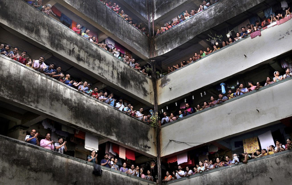 People clap from balconies in show of appreciation to health care workers at a Chawl in Mumbai, India, Sunday, March 22, 2020. (AP Photo/Rafiq Maqbool...