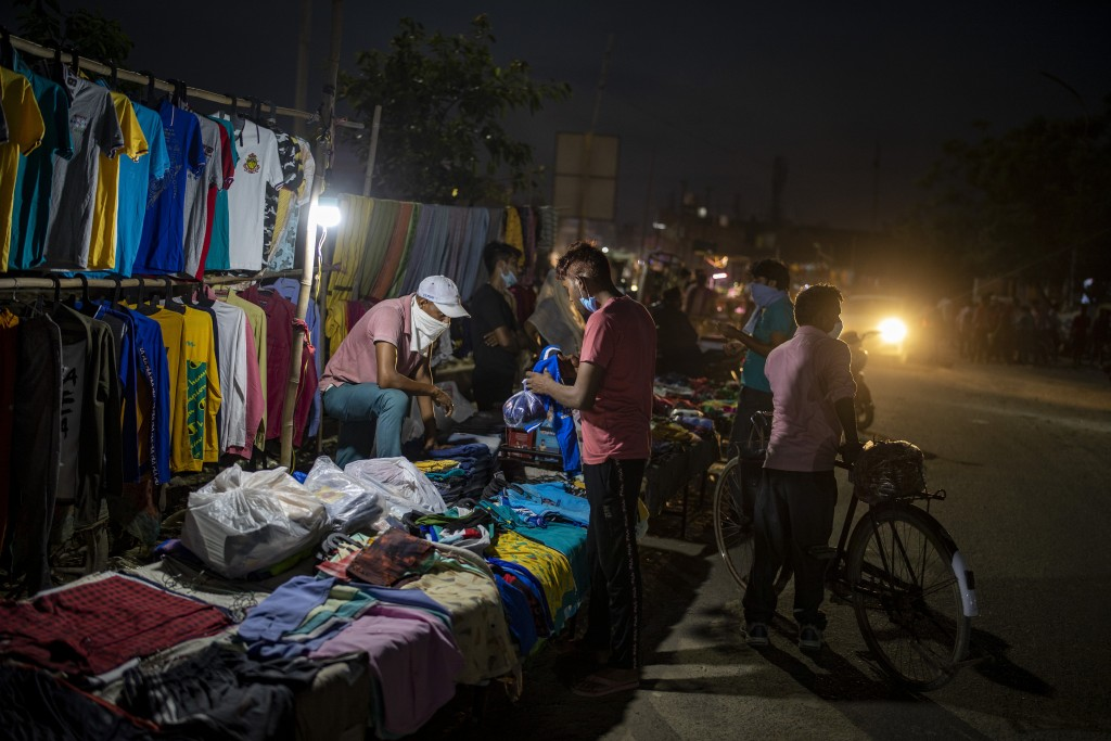 A roadside garments vendor covers his face with handkerchief as a precaution against the coronavirus at a daily evening market in Noida, outskirts of ...