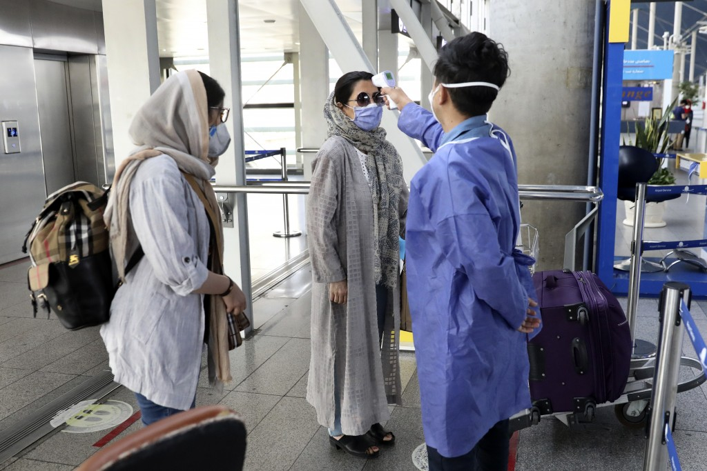 A health worker, right, checks temperature of passengers to help prevent the spread of the coronavirus upon arrival at the departure terminal of Tehra...