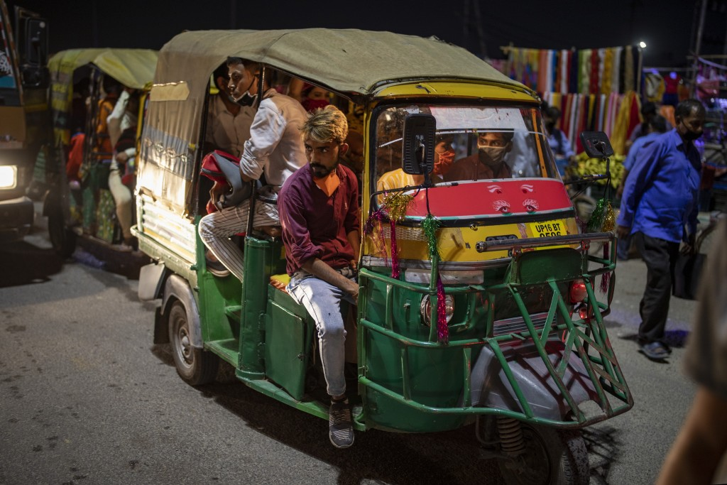 Commuters, some of them wearing masks as a precaution against the coronavirus ride an auto-rickshaw in Noida, outskirts of New Delhi, India, Thursday,...