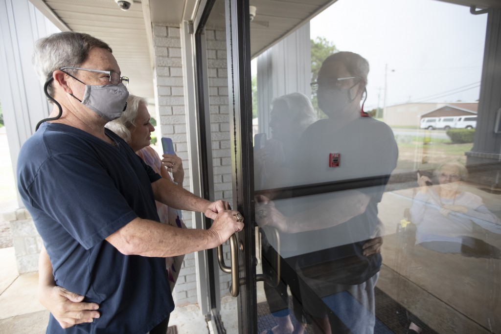 Southern Pines nursing home resident Shirley Campbell visits with her daughter, Margie Price, and son-in-law, Ken, through a glass door in Warner Robi...