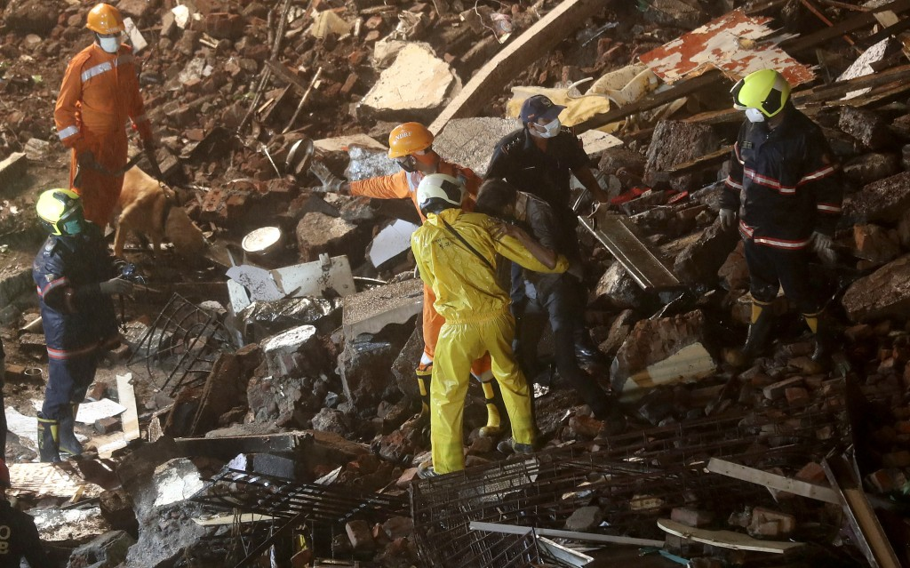 A man, center right, who got trapped in the debris is rescued from the site after a six-storey residential building collapsed in Mumbai, India, Thursd...