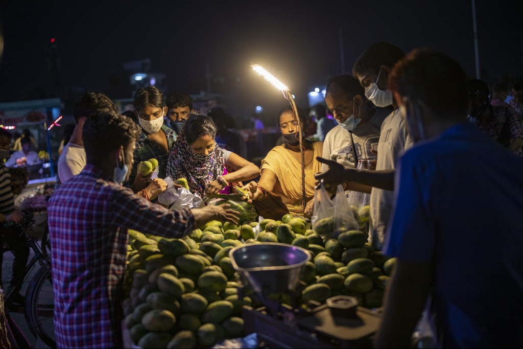 People wearing masks as a precaution against the coronavirus crowd a mango seller's stall at a daily evening market in Noida, outskirts of New Delhi, ...