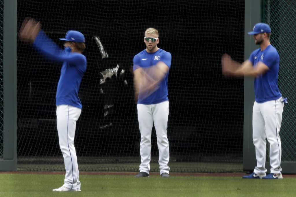 Kansas City Royals' Adalberto Mondesi, left, Hunter Dozier, center, and Bubba Starling stretch during baseball practice at Kauffman Stadium, Thursday,...