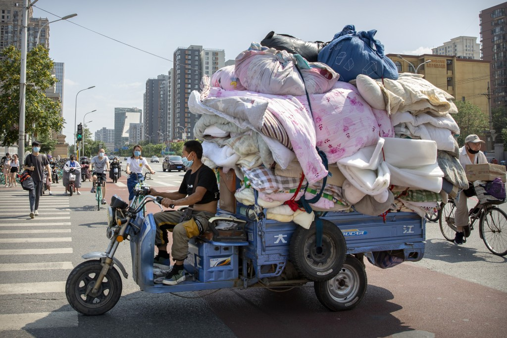 A man wearing a face mask to protect against the new coronavirus drives a cart loaded with fabric in Beijing, Tuesday, July 14, 2020. Health experts a...