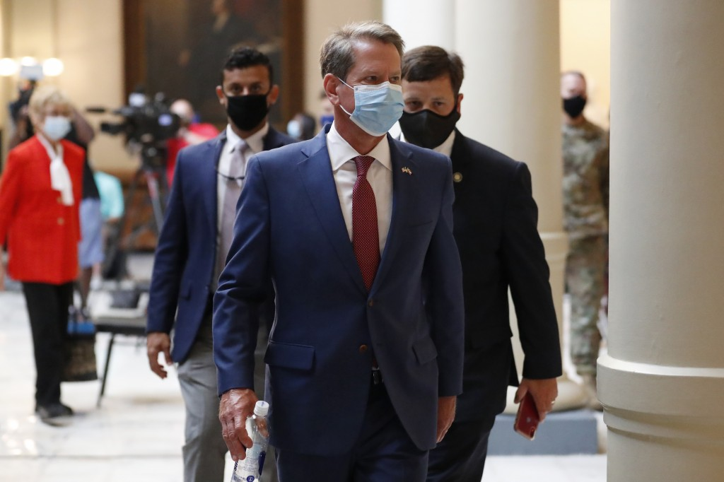 Georgia Gov. Brian Kemp returns to his office after giving a coronavirus briefing at the Capitol Friday, July 17, 2020, in Atlanta.  Kemp is suing Atl...