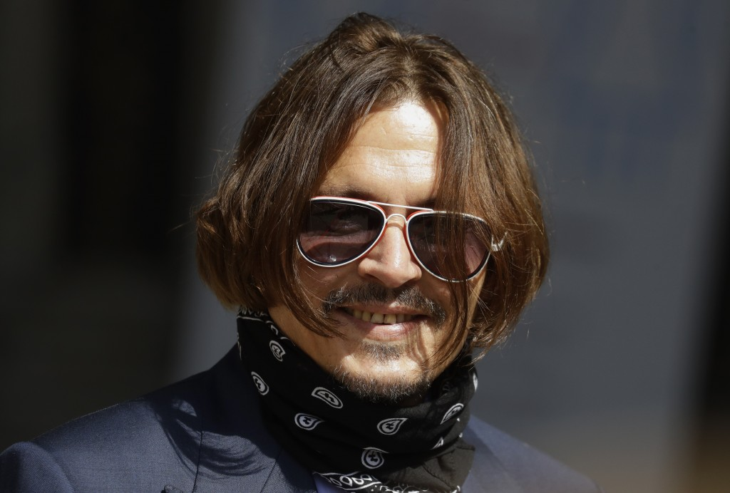 Actor Johnny Depp smiles he arrives at the High Court in London, Friday, July 17, 2020. Depp is suing News Group Newspapers, publisher of The Sun, and...