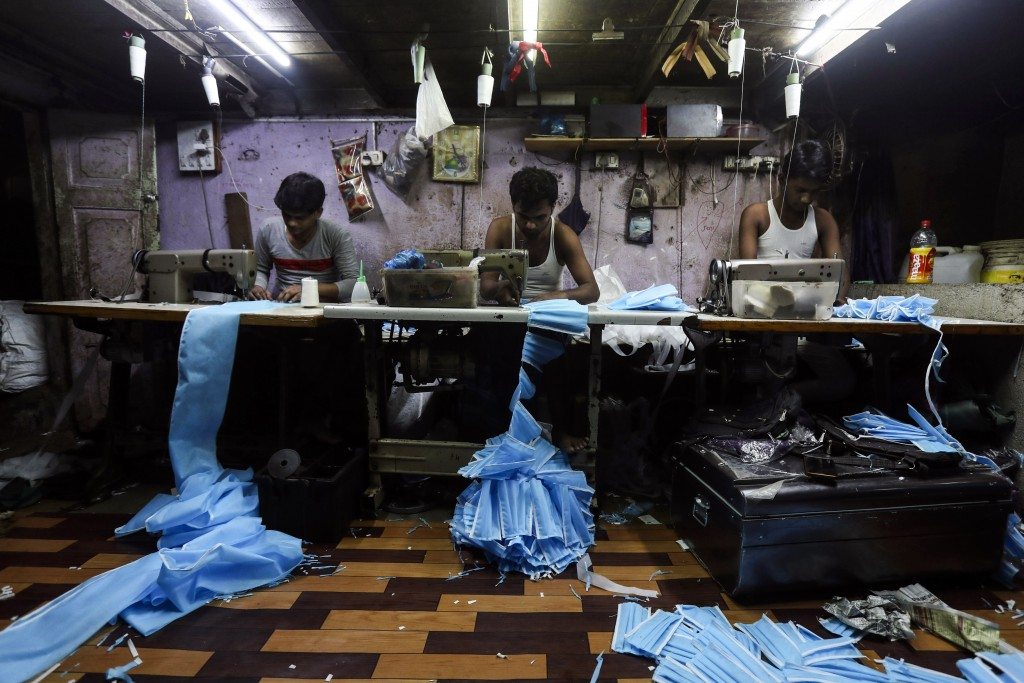 Indian workers make face masks which are in demand due to the coronavirus at a private manufacturing unit in Mumbai, India, Tuesday, March 17, 2020. (...