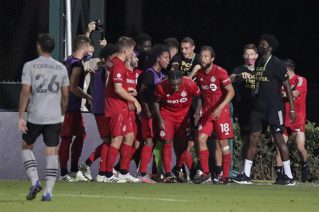 Toronto FC forward Ayo Akinola, center, celebrates with teammates after scoring his third goal of the game during the second half of an MLS soccer mat...