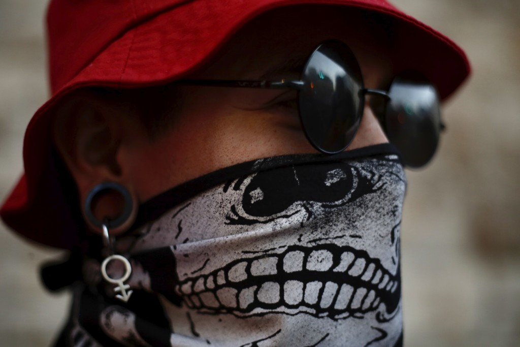 A protester wears a face mask amid the Coronavirus in front of Israel's Prime Minister's residence in Jerusalem, Thursday, July 16, 2020. Hundreds of ...