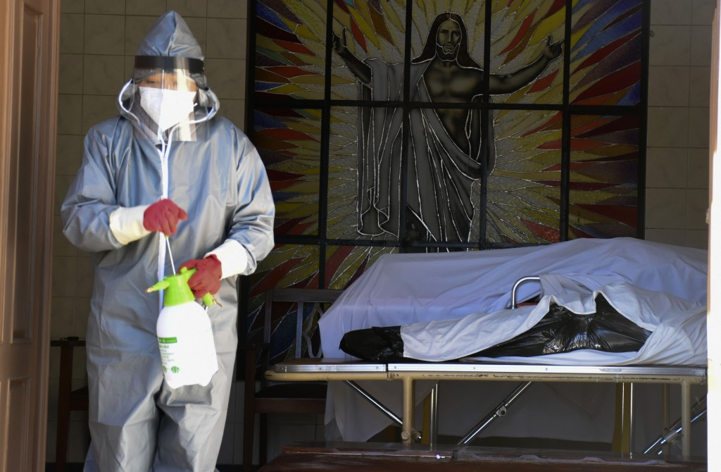 A health worker disinfects the area next to a coffins with the remains of a recently deceased resident of the San Jose nursing home in Cochabamba, Bol...