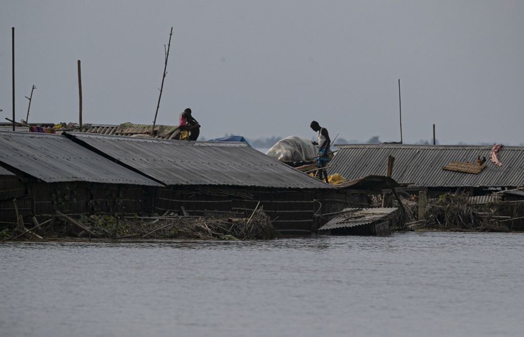 Flood affected people tare seen on the roof of their partially submerged houses along river Brahmaputra in Morigaon district, Assam, India, Thursday, ...