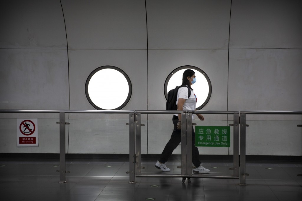 A woman wearing a face mask to protect against the coronavirus walks through a subway station in Beijing, Friday, July 17, 2020. Further restrictions ...