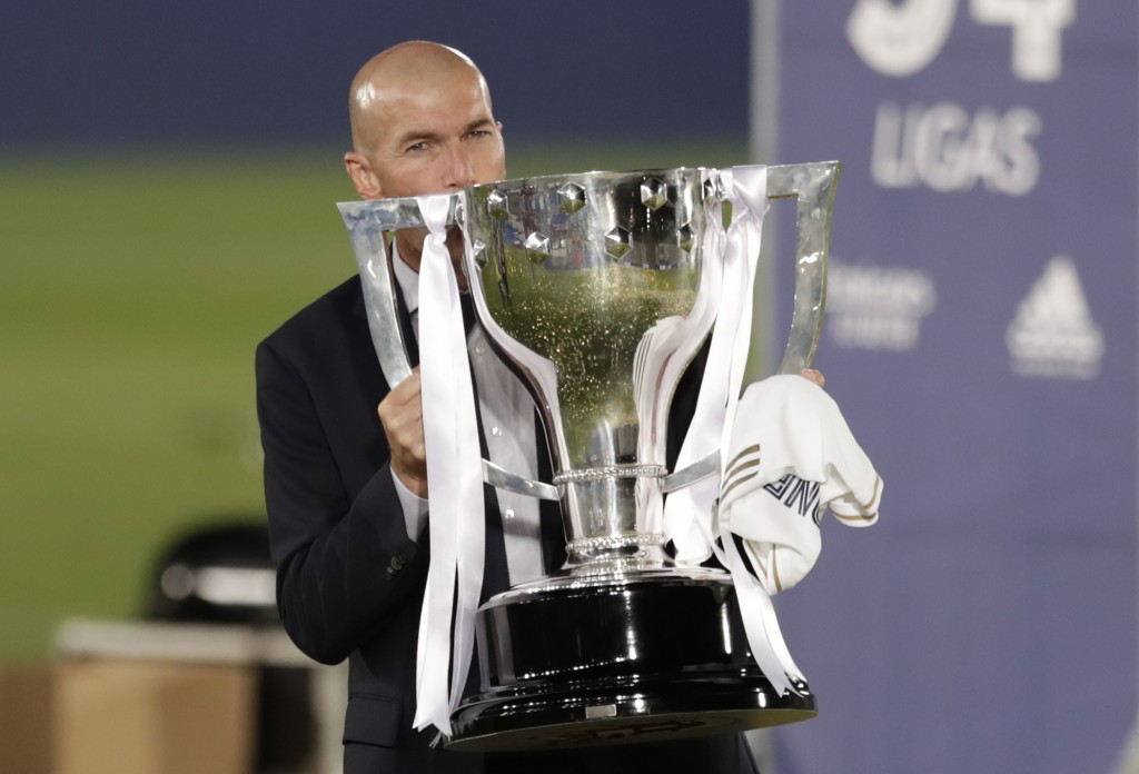 Real Madrid's head coach Zinedine Zidane, holds the trophy as he poses for the photographers after winning the Spanish La Liga 2019-2020 following a s...