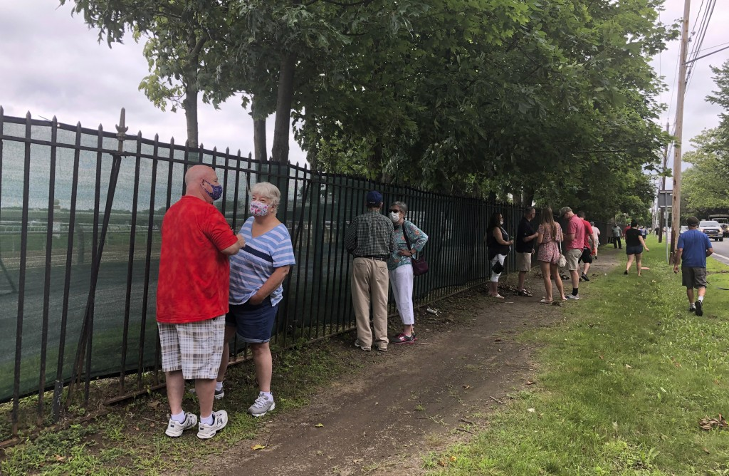 Horse racing fans talk along the fence outside Saratoga Race Course in Saratoga Springs, N.Y., Thursday, July 16, 2020. A Saratoga season like no othe...