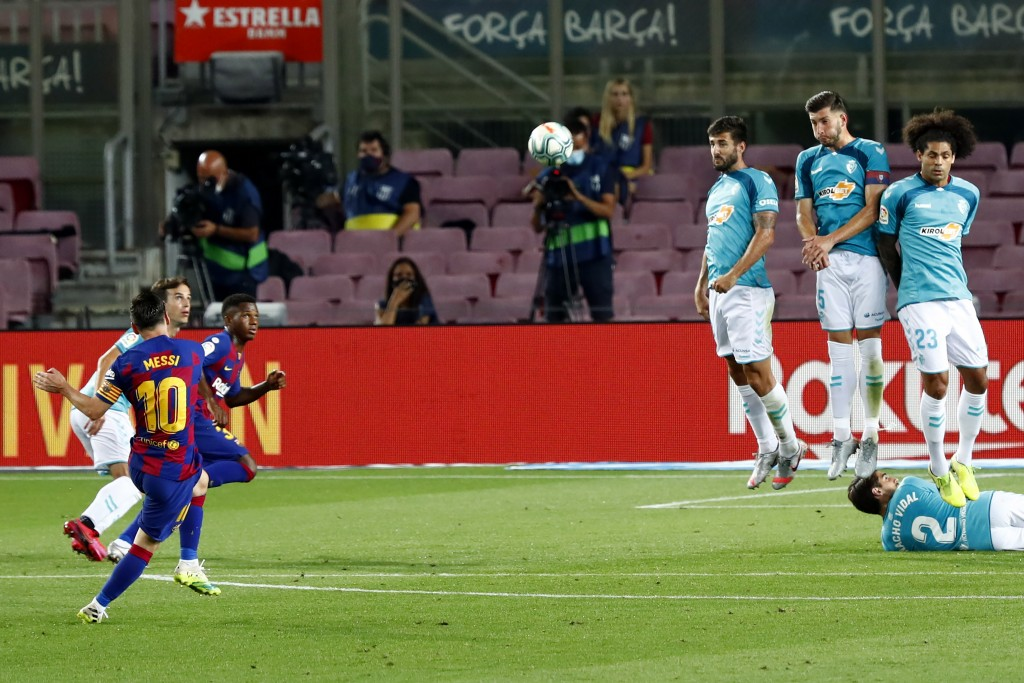 Barcelona's Lionel Messi scores against Osasuna during a Spanish La Liga soccer match between Barcelona and Osasuna at the Camp Nou stadium in Barcelo...