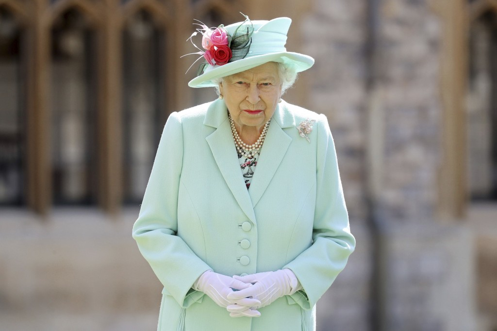 Britain's Queen Elizabeth looks on after awarding Captain Sir Thomas Moore his knighthood during a ceremony at Windsor Castle in Windsor, England, Fri...