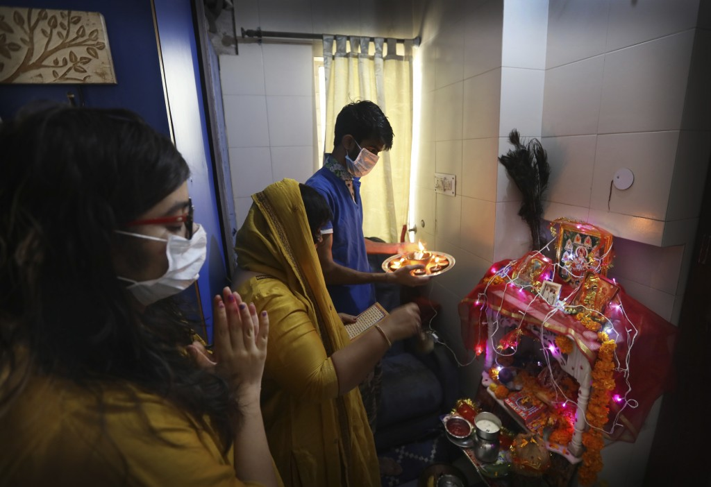 A family, wearing face masks as a precaution from coronavirus, pray inside their house marking the start of Navratri festival, where Hindu fast for ni...