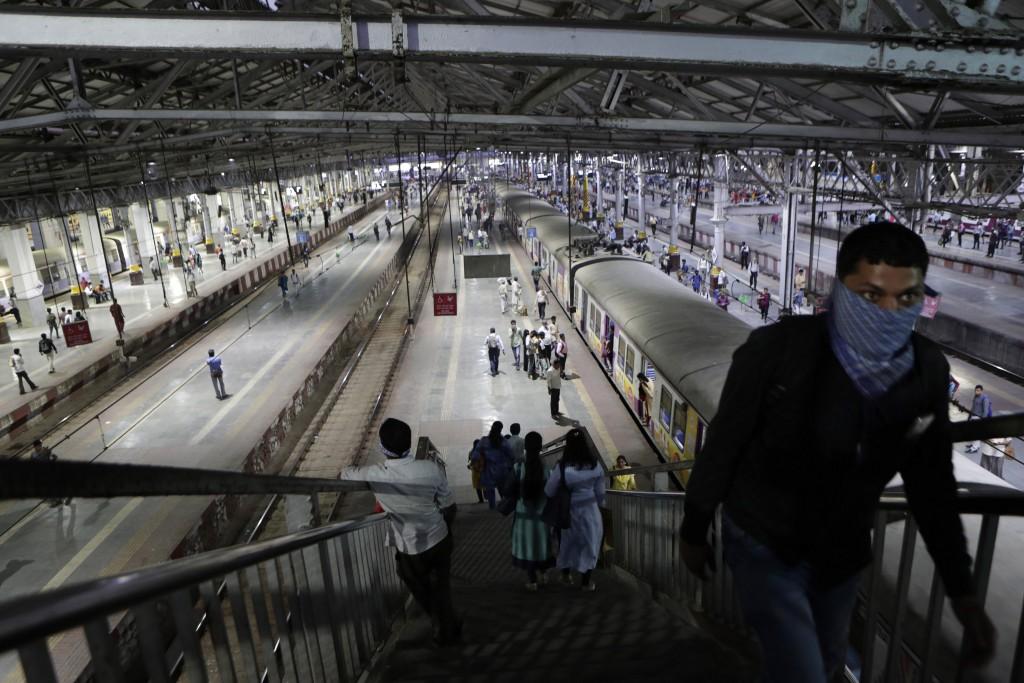 A passenger climbs the stairs of a fairly empty Chhatrapati Shivaji Maharaj Terminus train station during the coronavirus outbreak in Mumbai, India, T...