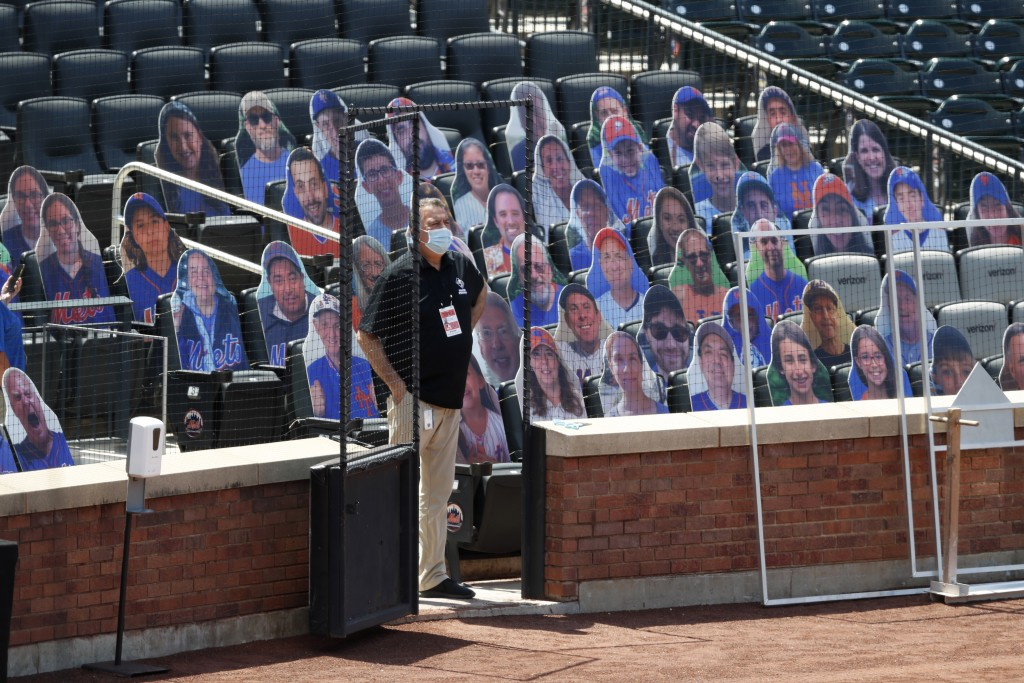 A New York Mets employee stands beside cardboard cutouts of people to simulate of fans in the stands during baseball practice at Citi Field, Thursday,...
