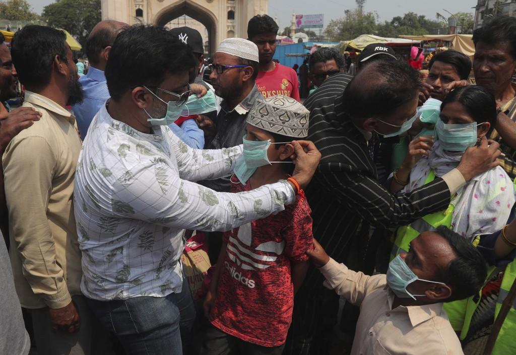 Indian social activists distribute masks to pedestrians at the landmark Charminar in Hyderabad, India, Thursday, March 5, 2020. (AP Photo/Mahesh Kumar...