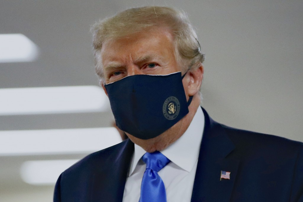 FILE - In this Saturday, July 11, 2020, file photo, President Donald Trump wears a face mask as he walks down a hallway during a visit to Walter Reed ...