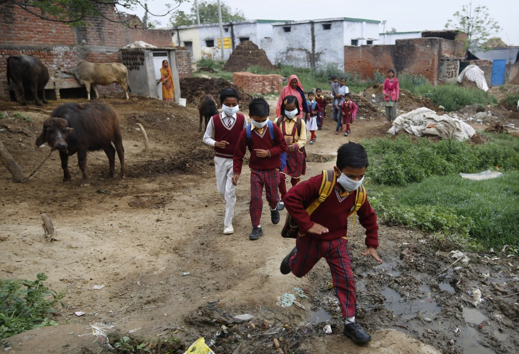 Children wearing face masks amid concerns over the spread of the coronavirus, return home after learning that public gatherings and schools are shut f...