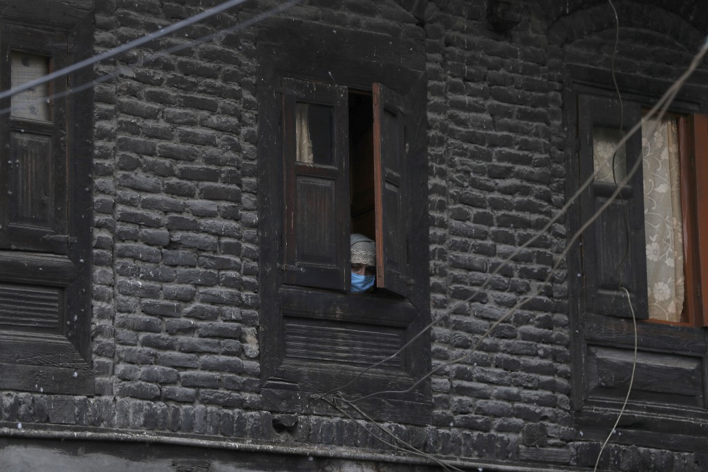 A Kashmiri woman wearing protective mask watches through a window of her house as an Indian policeman makes markings for people to maintain social dis...