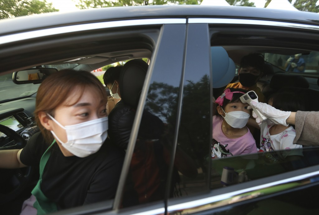 A young girl has her temperature checked as she arrives to watch a drive-in concert at the Gyeongbok Palace parking lot in Seoul, South Korea, Friday,...