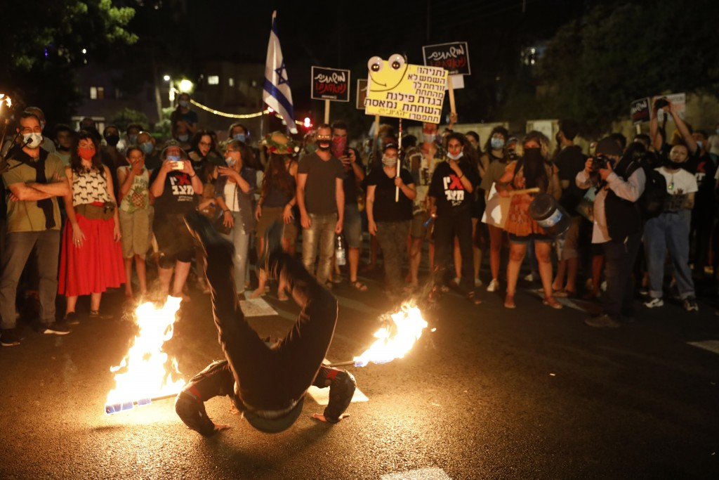 A performer dance with fire during a protest in front of Israel's Prime Minister's residence in Jerusalem, Thursday, July 16, 2020. Hundreds of protes...