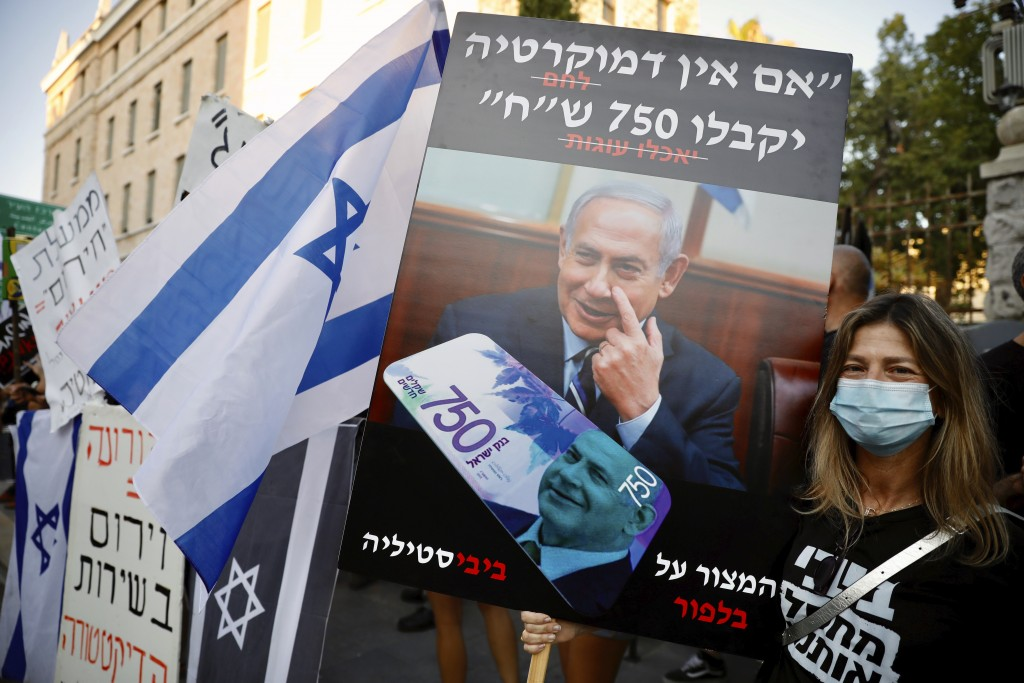 """A protester holds a sign that reads """"If there's no democracy, people will get 750 shekels (about $200),"""" in front of Prime Minister Benjamin Netanyahu..."""