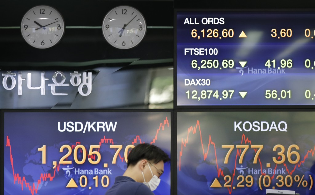A currency trader wearing a face mask watches computer monitors near the screens showing the foreign exchange rate between U.S. dollar and South Korea...