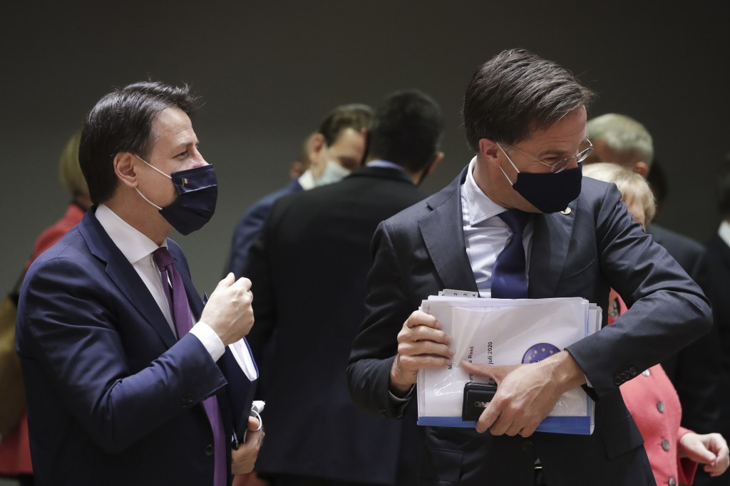 Italy's Prime Minister Giuseppe Conte, left, speaks with Dutch Prime Minister Mark Rutte during a round table meeting at an EU summit in Brussels, Fri...