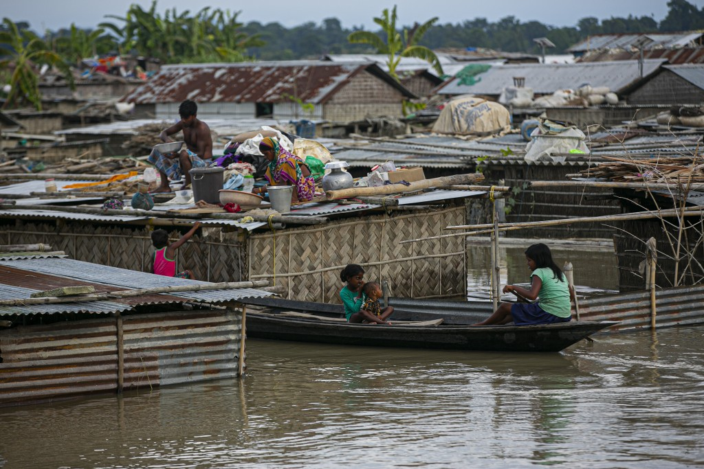 A flood affected family takes shelter on the roof of their partially submerged house along river Brahmaputra in Morigaon district, Assam, India, Thurs...